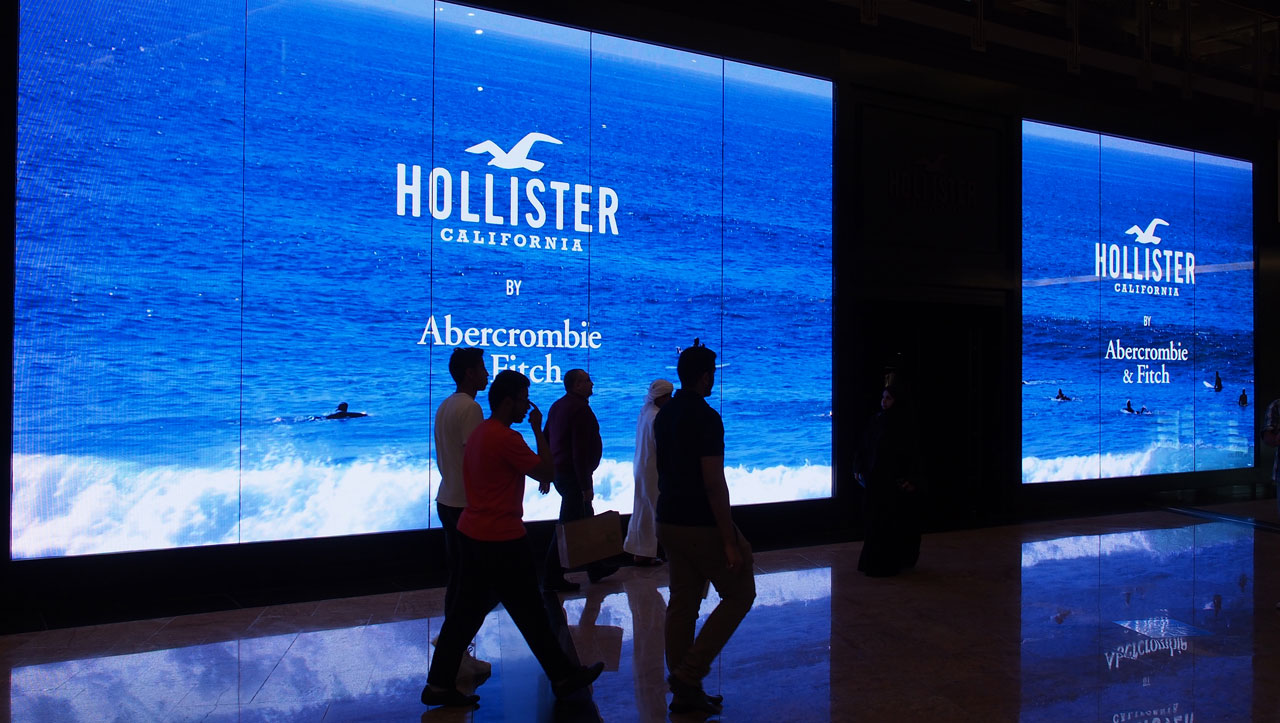Hollister shop storefront with large screens displaying a beachfront