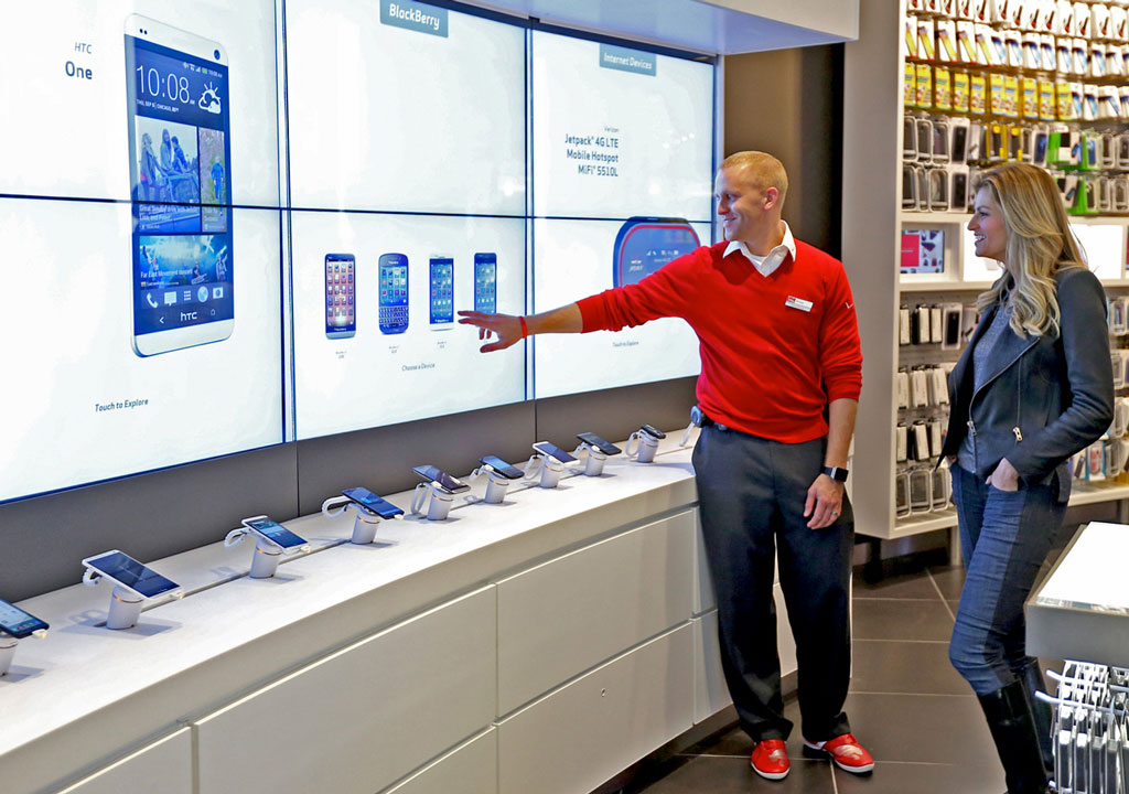 A Verizon Salesperson interacting with a customer and a digital wall